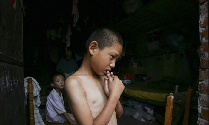 A mentally handicapped child waits to get dressed after bathing at the Wang Jiayu Orphanage which was set up by a farmer in Sanshilipu Village of Anhui Province, China. In a recent report by Human Rights Watch group, 28 percent of disabled children are not receiving the basic education they are entitled too.  (China Photos/Getty Images)