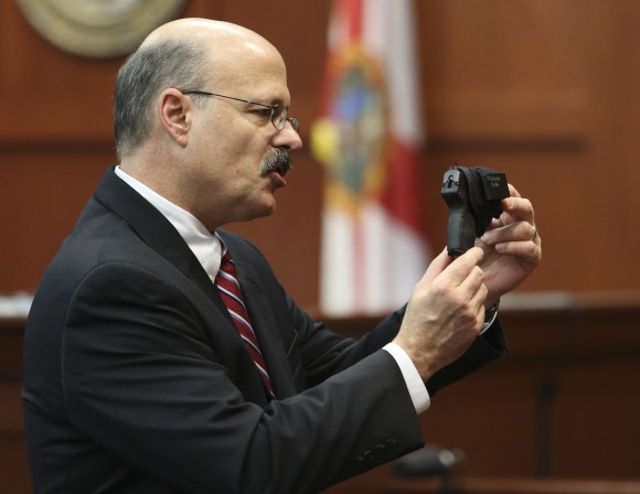 Assistant state attorney Bernie de la Rionda shows George Zimmerman's gun to the jury while presenting the state's closing arguments against Zimmerman during his trial in Seminole circuit court in Sanford, Fla. Thursday, July 11, 2013. Zimmerman has been charged with second-degree murder for the 2012 shooting death of Trayvon Martin. (AP Photo/Orlando Sentinel, Gary W. Green, Pool)