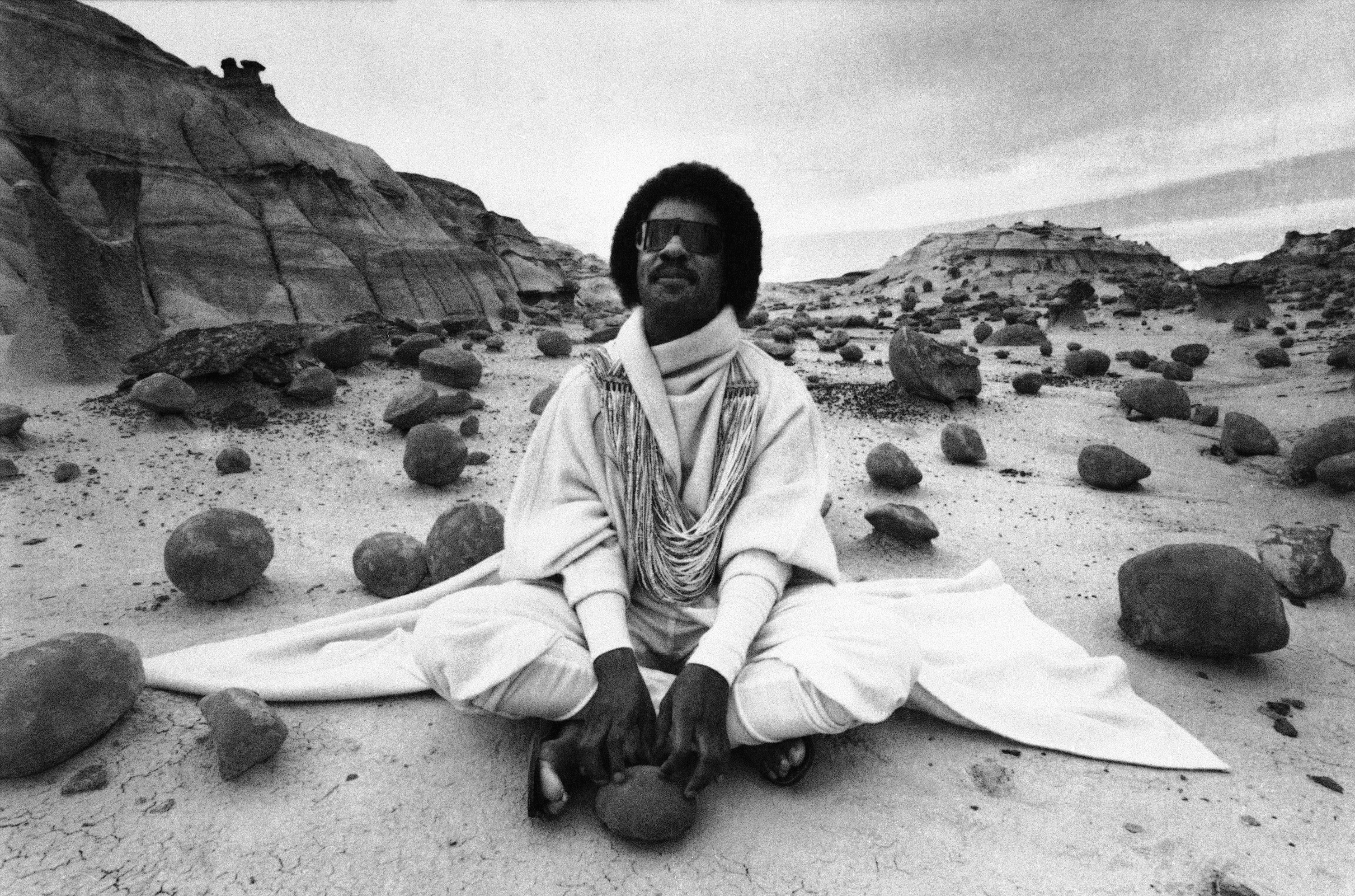 Musician Stevie Wonder sits amidst the eerie rocks of the Bisti Badlands in Farmington, New Mexico, Sept. 1, 1982, filming a commercial probably never seen in the United States. (AP Photo)