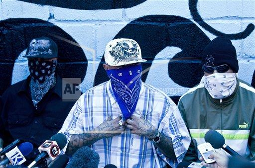 Masked members of the 18th Street gang give a press conference inside the San Pedro Sula prison in Honduras, Tuesday, May 28, 2013. Honduras' largest and most dangerous street gangs have declared a truce, offering the government peace in exchange for rehabilitation and jobs. A Mara Salvatrucha spokesman says the gang and a rival known as 18th Street will commit to zero violence and zero crime in the streets as first step show of good faith. (AP Photo/Esteban Felix)
