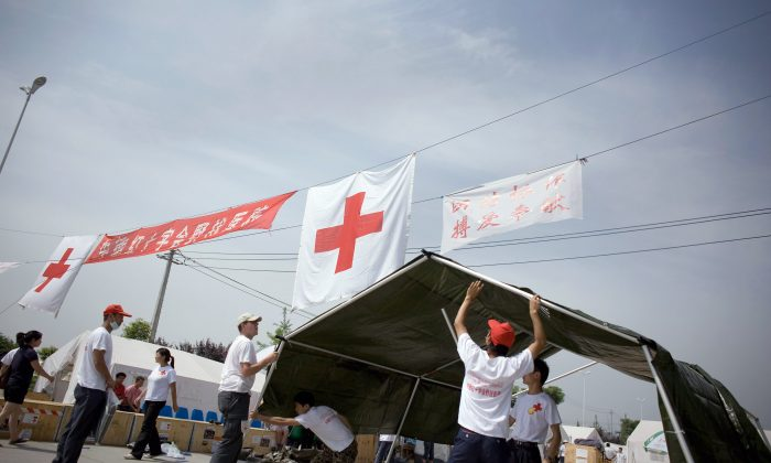 German engineers and their Chinese counterparts build a reception tent at a field hospital in Sichuan Province, China. The Chinese Red Cross has been charging hospitals for arranging organ transplants, according to a report by The Beijing News. (Andrew Wong/Getty Images)