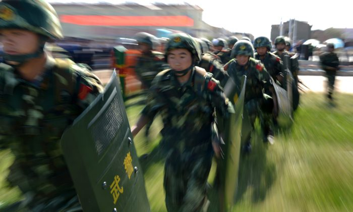 """An anti-terrorism force including public security police and the armed police attend an anti-terrorism joint exercise in Hami, northwest China's Xinjiang region on July 2, 2013. At least 15 Uyghurs were killed in an """"anti-terrorist"""" raid on Aug. 20 in Kashgar Prefecture. (STR/AFP/Getty Images)"""