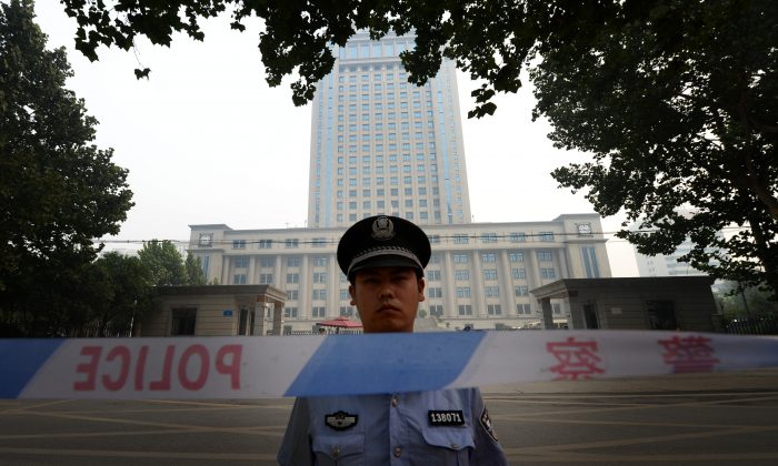 A police officer stands guard at the Intermediate People's Court in Jinan, Shandong Province, China, on Aug. 24, 2013. (Mark Ralston/AFP/Getty Images)