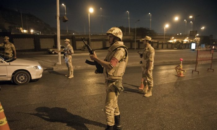 Egyptian troops keep watch at a checkpoint during the curfew hours in Cairo late on Aug. 19. (KHALED DESOUKI/AFP/Getty Images)