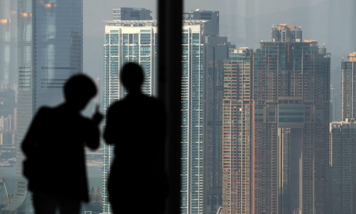 Two people are silhouetted as they look towards residential properties on the Kowloon peninsula from Hong Kong island on October 27, 2010. A new report lists 315 Chinese who are worth over $1 billion, a surprising number considering 10 years ago there was none listed in China.  (ANTONY Antony Dickson/AFP/Getty Images)