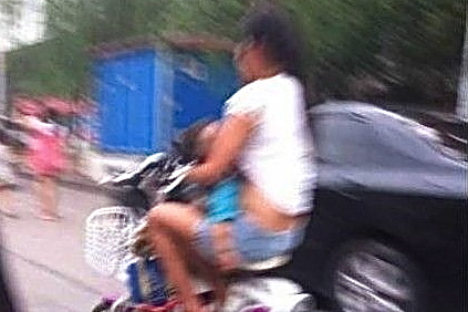 Screenshot showing the woman breastfeeding her baby with one hand, while driving her moped with the other. (Screenshot/Epoch Times)