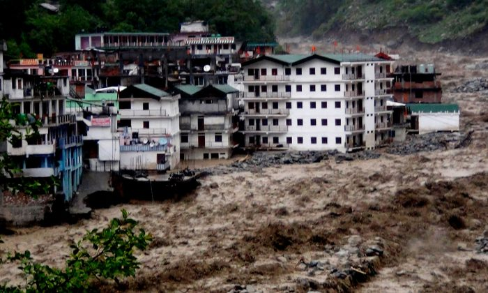 Fast moving water from the  Alaknanda river destroys building during a heavy monsoon rain in Govindghat town in the Indian state of Uttrakhand on June 17, 2013. Environmental engineer G. D. Agarwal started an indefinite fast to stress his demand for the government to scrap all hydro projects on the Bhagirathi, Alaknanda, and Mandakini head-streams of the Ganges.(STRDEL/AFP/Getty Images)