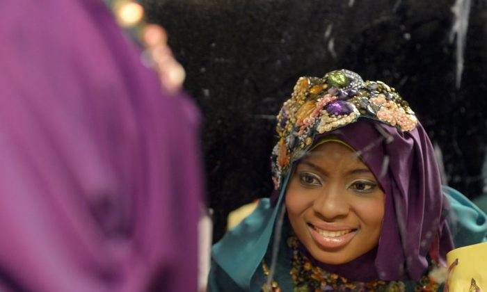 Contestant of the Muslimah World 2013, Obabiyi Aishah Ajibola of Nigeria, checks her make-up in a mirror while contestants wait for a grand final during the Muslimah World competition in Jakarta on September 18, 2013. (ADEK BERRY/AFP/Getty Images)
