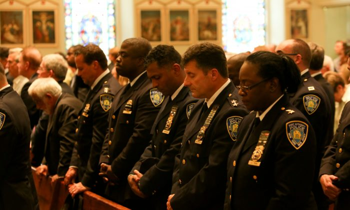Port Authority Police Department officers attend an interfaith service at St. Peter's Church on Sept. 11, 2013, in remembrance of the employees of the Port Authority of New York and New Jersey who died on 9/11. Eighty-four employees, including 37 police officers, lost their lives in One World Trade Center on Sept. 11, 2001.  (Christian Watjen/Epoch Times)
