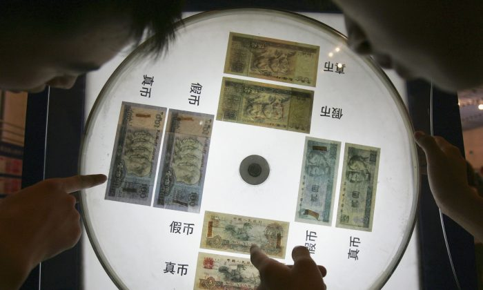 Visitors view a show window displaying yuan notes and telling visitors how to identify real and fake notes at an exhibition of the Chinese currency Yuan at the Beijing Science Museum on July 22, 2005 in Beijing, China. (China Photos/Getty Images)