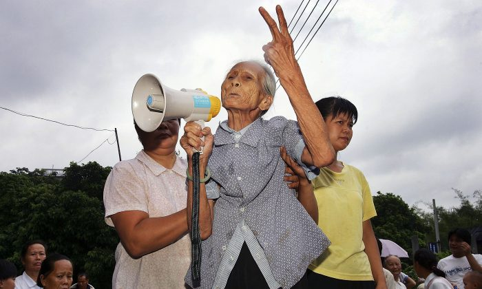 An octogenarian grandmother gets up on a pile of rocks in her bare feet to give a speech against the corruption of the village secretary, at a villagers' meeting of Taishi Village on July 31, 2005 in Guangzhou of Guangdong Province. Ma Qiang argues that such abuses of power are common. (China Photos/Getty Images)