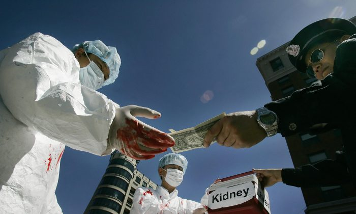Chinese activists dramatize an illegal act of paying for human organs during a protest April 19, 2006 in Washington, D.C. (Jim Watson/AFP/Getty Images)