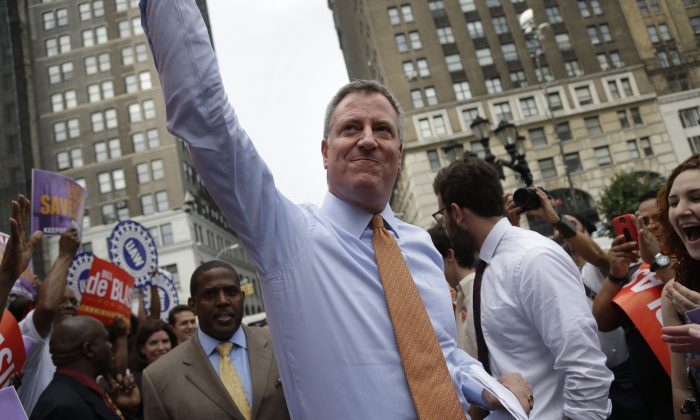 Democratic mayoral candidate Bill de Blasio, center, arrives at a rally in Brooklyn, New York City, Sept. 12, 2013. De Blasio, who has been the most vocally anti-Bloomberg of the major candidates, emerged from Tuesday's primary election as the Democratic front-runner. (AP Photo/Seth Wenig)