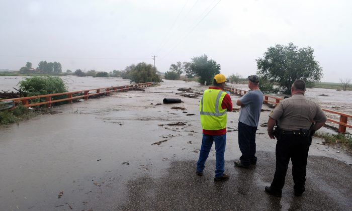 Observers from the Chaves County Sheriff's Department and the City of Roswell watch as Berrendo Creek begins to spill over the N. Red Bridge Road bridge in Roswell, New Mexico, Wednesday, September 11, 2013. (Mark Wilson  Roswell Daily Record)