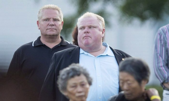 Toronto Mayor Rob Ford stands with his brother, Councillor Doug Ford, at a Conservative Party BBQ in Toronto on August 29, 2013. Canada's two largest newspapers acted responsibly and in the public interest in reporting on drug allegations against the brothers, the Ontario Press Council has ruled. (The Canadian Press)
