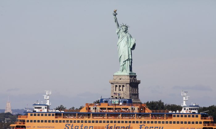 In this Oct. 1, 2012 file photo, the Staten Island Ferry passes the Statue of Liberty as it crosses New York Harbor. (Mark Lennihan/AP Photo)