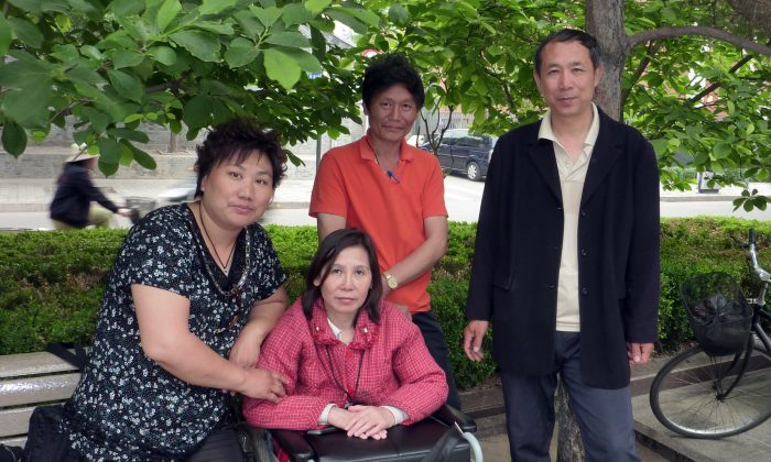 Ni Yulan (C) and her husband, Dong Jiqin (2nd R), pose with a supporter during an interview at the Imperial City Heritage Park in Beijing, May 27, 2010. Ni was released on Oct. 3 after serving a two-and-a-half-year sentence for her human rights activism. (Robert J. Saiget/AFP/Getty Images)