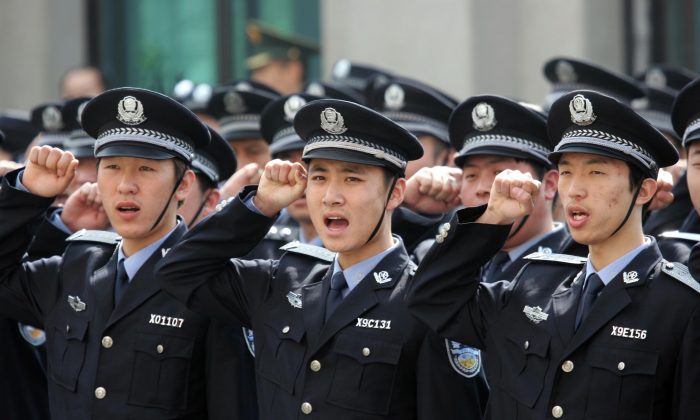 Police officers salute the flag of the People's Republic of China in 2011 in Liaoning Province. The Communist Party has recently launched a new mobilization campaign that will strike hard against perceived enemies of social order. (ChinaFotoPress/Getty Images)