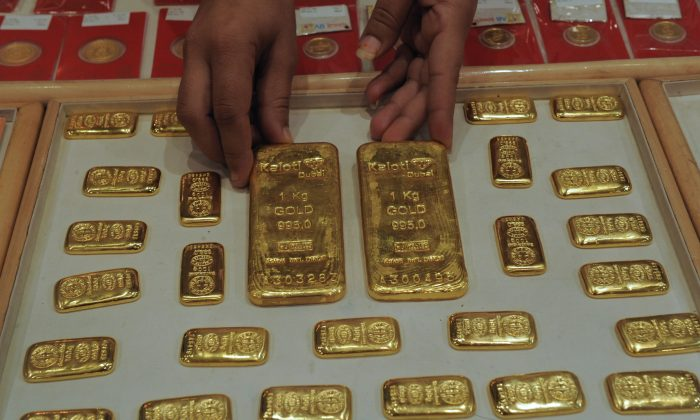 An Indian saleswoman arranges gold bars at a jewelry store in Ahmedabad on October 20, 2011. Taking clue from the dream of a sage in a village, the Indian government is planning to unearth 1000 tons of Gold treasures supposedly hidden under ruins, according to a Reuters report. (Sam Panthaky/AFP/Getty Images)