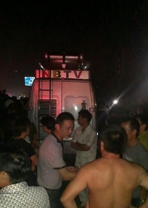 The NBTV van is stopped by crowds angry at a reporter's false report about the flooding in Zhejiang Province, on Oct. 11, 2013. (Weibo.com)
