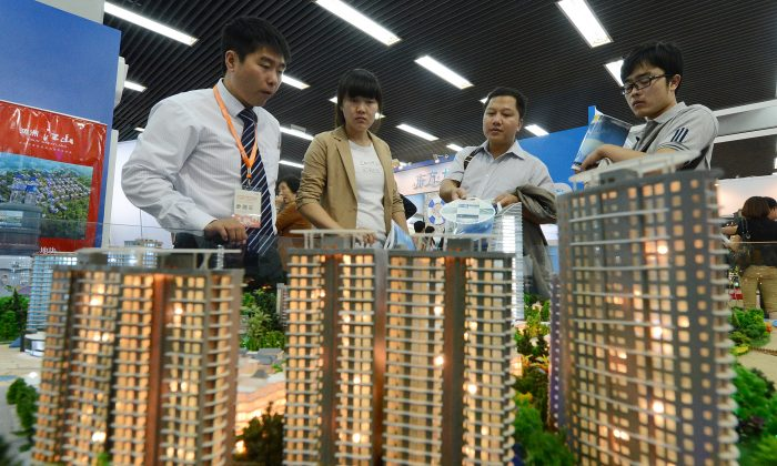 People view a model of a property development being sold at the Beijing Property and Investment Show on Sept. 20, 2012. The well-known Chinese financial columnist Niu Dao predicts that China's housing and asset bubbles will cause an economic crisis that will bring down the Chinese regime. (Mark Ralston/AFP/GettyImages)