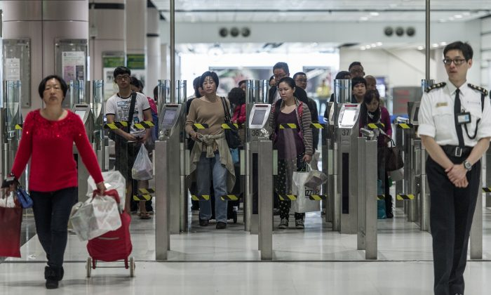 People proceed to an immigration checkpoint at a border crossing point of mainland China with Hong Kong on March 1, 2013. Hong Kong has no control over who immigrates to it from China. (Philippe Lopez/AFP/Getty Images)