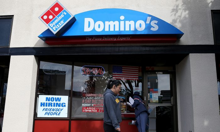 A 'Now Hiring' sign is posted in the window of a Domino's Pizza restaurant on in Albany, Calif., March 8. (Justin Sullivan/Getty Images)