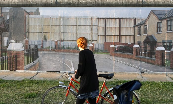 A visitor passes a photo of the Belfast Peace lines in Northern Ireland in the 'Wall on Wall' exhibition at the East Side Gallery section of the former Berlin Wall on July 10, 2013 in Berlin, Germany. (Adam Berry/Getty Images)