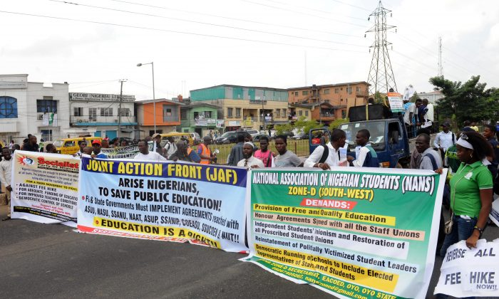 Students and workers carry placards as they march on the Lagos-Ikorodu highway to protest against the suspension of academic activities following a nation-wide strike embarked by lecturers in state-owned universities, on August 13, 2013 in Lagos. Students in collaboration with workers began mass protest to ask for quick resolution of conflicts that led to the on-going strike by lecturers in public Universities.  The Academic Staff Union of Universities (ASUU) had, on July 2, declared an indefinite strike over unresolved issues after the government allegedly breached a Memorandum of Understanding (MoU) they both signed in January 2011. (Pius Utomi Ekpei/AFP/Getty Images)