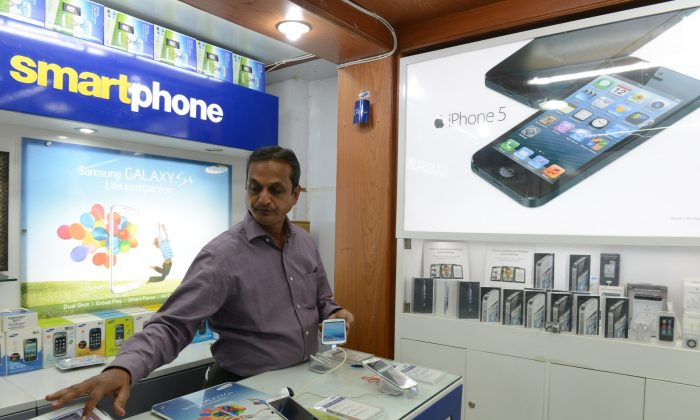 Indian vendor Madhusudhan Asawa looks at a display of smart phones at his mobile store in Secunderabad, the twin city of Hyderabad on August 28. Apple is looking to expand its market in India. (NOAH SEELAM/AFP/Getty Images)