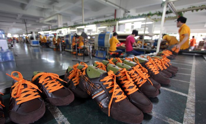Laborers work in a shoe factory in Jinjiang, in southern China's Fujian Province on Sept. 17, 2013. In a recent report the financial Consulting firm Deloitte says that due to China's slower economic growth, its domestic manufacturing sector is facing a cold winter. (STR/AFP/Getty Images)