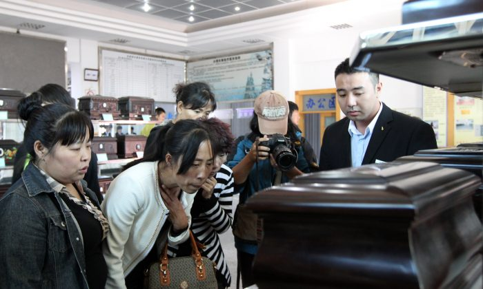 Zhang Jing (2nd L) chooses a box to hold the ashes of her husband Xia Junfeng, a 36-year-old street vendor, at Dongling Funeral Home on Sept. 26, 2013 in Shenyang, China. Xia Junfeng was executed for killing two urban management officers and injuring another in 2009. (ChinaFotoPress/Getty Images)