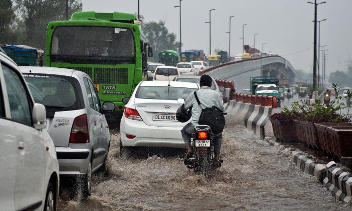 Vehicles drive along a water-logged road during heavy rain in New Delhi on September 26, 2013. The United Nations Intergovernmental Panel on Climate Change (IPCC) predicted in its recent report that the entire Indian subcontinent may witness longer rainy seasons in the second half of this century. (AFP PHOTO/ Prakash Singh)