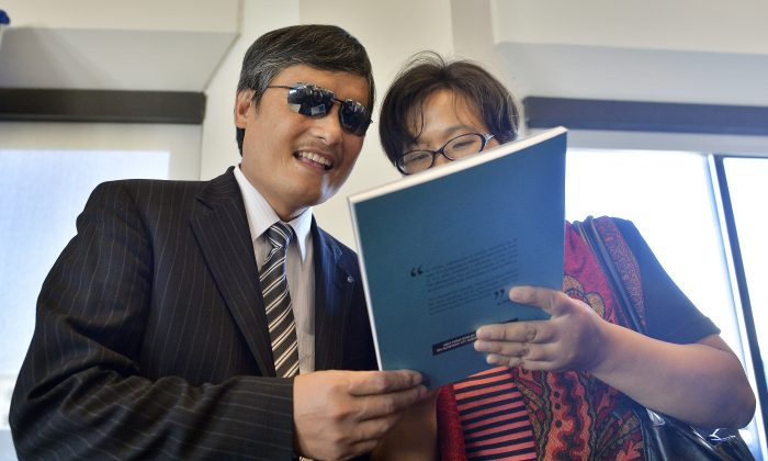Chen Guangcheng speaks with his wife Yuan Weijing before a press conference in Washington, DC, on Oct. 2, 2103. Chen took three positions at U.S. organizations from where he will continue his advocacy. (Jewel Samad/AFP/Getty Images)