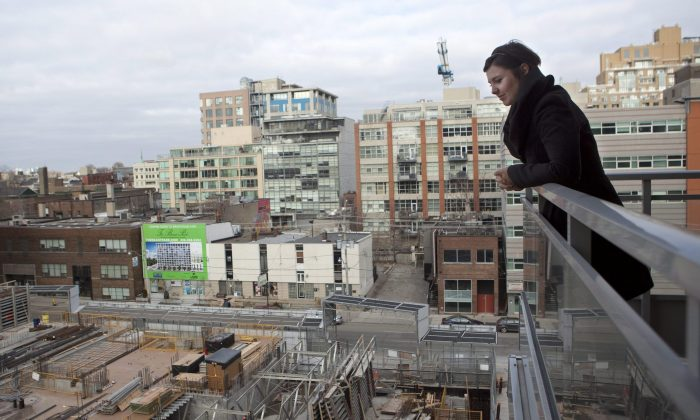 Condo owner Eva Kanovich looks onto a neighbouring condo under construction from her balcony in downtown Toronto in February 2012. The level of unsold new highrise condos remained large in recent months in the GTA, contributing to the fall in GTA housing starts in September reaching their lowest level in five months. (The Canadian Press/Pawel Dwulit)