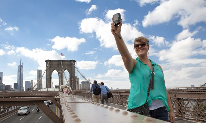 A girl takes a picture of herself on the Brooklyn Bridge, New York City, June 11, 2013. (Samira Bouaou/Epoch Times)