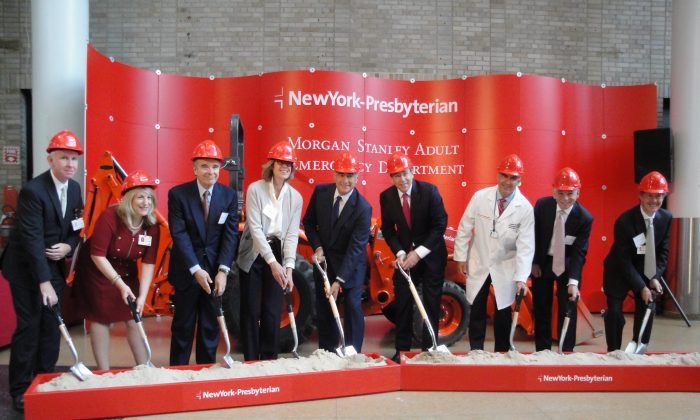Wearing hardhats for the ground breaking of the Morgan Department Adult Emergency Department at New York-Presbyterian (NYP)/Columbia University Medical Center in Washington Heights, New York City, Oct. 7, 2013: (L–R) Anthony Dawson, vice president of operations for NYP/Milstein; Andria Castellanos, senior vice president & chief operating officer for NYP/Milstein; Stephen Robert and Pilar Crespi Robert, trustees of the Source of Hope Foundation; John Mack, chairman of the board and former chairman and CEO of Morgan Stanley; Tom Nides, vice chairman of Morgan Stanley; James Giglio, director of emergency medicine at NYP/Columbia; Steven Corwin, CEO of NYP; Dr. Robert Kelly, president of NYP. (Sarah Matheson/Epoch Times)