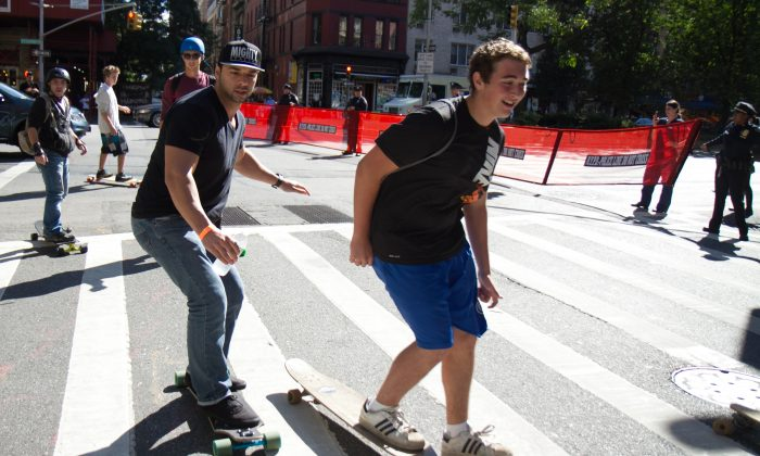 """The NYPD redirects skateboarders from riding down Broadway in their annual """"Broadway Bomb."""" Skaters gather every year 116th Street and ride down Broadway all the way to Wall Street in New York City. (Benjamin Chasteen/Epoch Times)"""