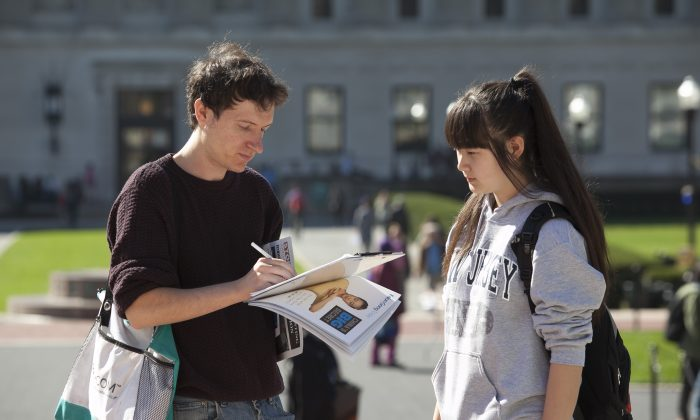 Stephen Petro signs the petition in support of H.Res. 281 to stop forced organ harvesting of Falun Gong practitioners in China, set up by the Falun Dafa Club, on the stairs of Low Memorial Library at Columbia University, New York, Oct. 15, 2013. (Samira Bouaou/Epoch Times)