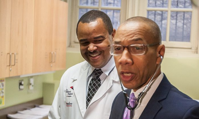 New York City Department of Education Chancellor Denis Walcott (R) tours the facilities of the new school health center with Shawn Bowen, the center's pediatrician, in Morris Educational Campus in the South Bronx, New York, Oct. 21, 2013. (Petr Svab/Epoch Times)