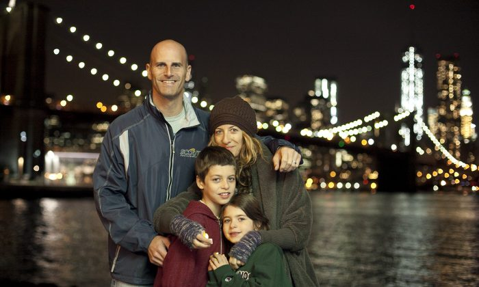 Michael Neuman and Jennifer Aks-Neuman with their children, Alex Neuman, 9, and Naia Neuman, 6, attend a candlelight vigil in DUMBO, commemorating one year since Superstorm Sandy hit New York, Oct. 29, 2013. (Samira Bouaou/Epoch Times)