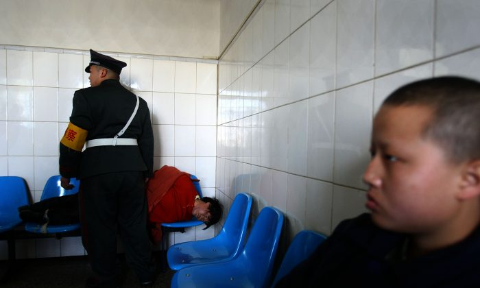 A man who was just escorted to the Kunming Mental Hospital lies on chairs on Dec. 1, 2007, in Kunming of Yunnan Province, southwest China. A new mental health law is supposed to curb the practice of involuntarily admitting patients to psychiatric hospitals, but the law's vagueness leaves room for continued abuses. (China Photos/Getty Images)