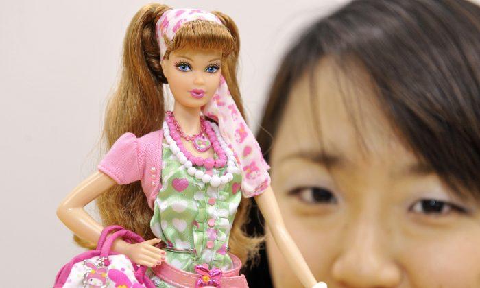 An employee of Mattel's Japanese subsidiary Mattel International displays a Barbie doll in Tokyo in 2008.  (Yoshikazu Tsuno/AFP/Getty Images)