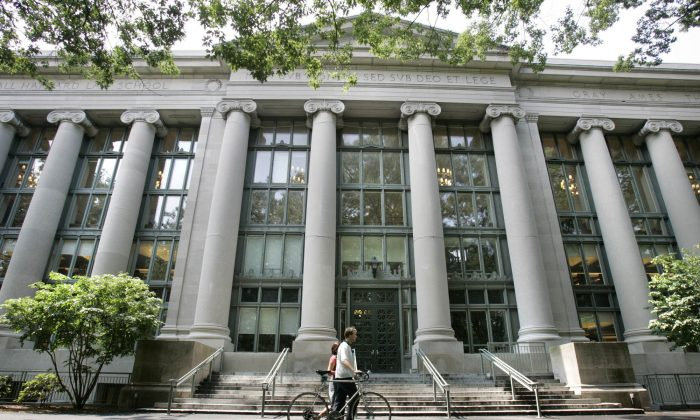 A bicyclist walks by Langdell Hall, the Harvard Law Library, on the campus of the Harvard Law School in Cambridge, Mass. in a file photo. Law school admissions are declining due to shrinking job market for lawyers. (AP Photo/Charles Krupa)