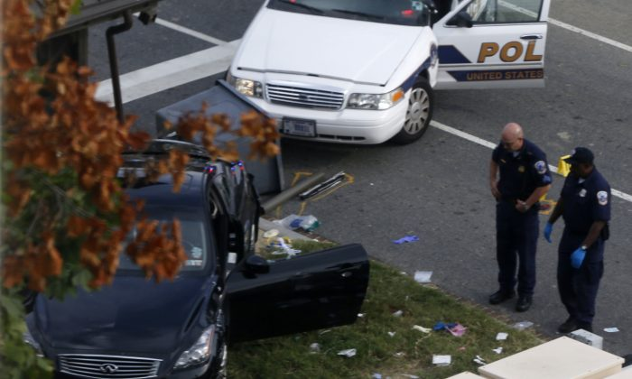 The black car driven by the suspect--identified as Miriam Carey--in the Washington D.C. car chase on Thursday, with Capitol Hill police officers nearby. Carey has been identified by law enforcement sources as the woman who was driving the car and was fatally shot by police. (AP Photo/Charles Dharapak)