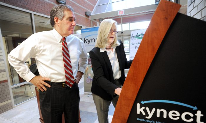 Carrie Banahan, executive director of Kentucky's Health Benefits Exchange, shows a Kynect information kiosk to Lt. Gov. Jerry Abramson in Owensboro, Ky., Oct. 3. (AP Photo/The Messenger-Inquirer, Gary Emord-Netzley)