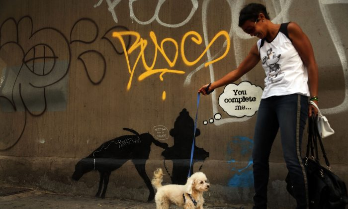 A woman poses in front of a new Bansky work on a side of a wall in New York City on October 3, 2013. (Spencer Platt/Getty Images)