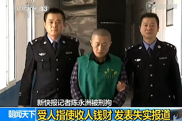 Chenyongzhou-police: Chen Yongzhou, a reporter at New Express, is taken by two policeman to make a confession on the state broadcaster on Oct. 26. He is handcuffed, wearing a prison suit, with a shaved head. (v.qq.com/screenshot/Epoch Times)