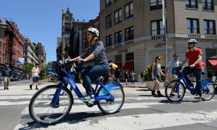 A couple ride their Citi Bike bicycles from a station near Union Square as the bike sharing system is launched in New York on May 27, 2013. (Stan Honda/AFP/Getty Images)