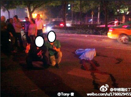 Two Chinese men posed next to the body of a car crash victim in Shaanxi Province. One was tracked down by a reporter, and claimed not to remember the incident because they were drunk at the time. (Weibo.com)